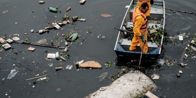 Environment Institute of Rio de Janeiro State (INEA) staffers collect a bed mattress as the tide moves...