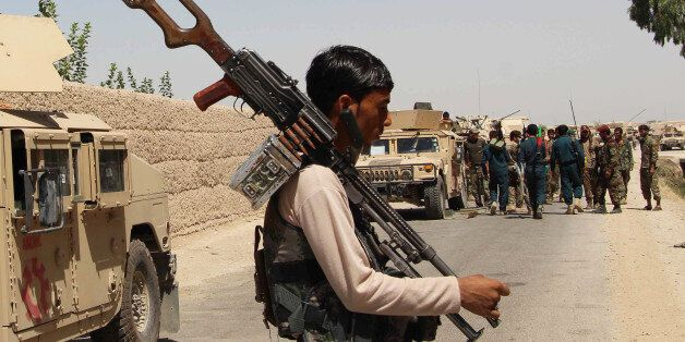 Afghan security personnel prepare for combat during an ongoing battle with Taliban militants in the Nad...