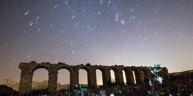 ANTALYA, TURKEY - DECEMBER 14: Perseid meteor streaks across the sky above historical aqueduct at ancient...