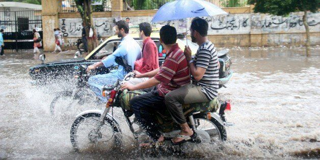 KARACHI, PAKISTAN - AUGUST 06: Pakistani people are seen in flood water after a torrential rain caused...