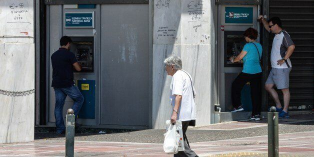 People withdraw money from ATMs in downtown Athens on July 5, 2015. Greek voters headed to the polls...
