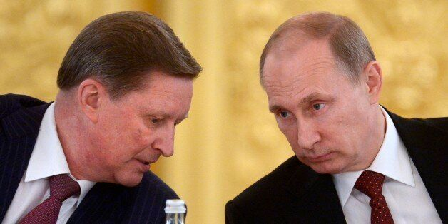 Kremlin's Chief of Staff Sergei Ivanov, left, speaks to Russian President Vladimir Putin during a Council...