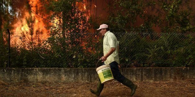 A villager runs with a bucket to takle a wildfire in Soutelo near Macinhata do Vouga, central Portugal,...