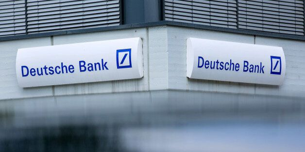 The Deutsche Bank AG logo sits on the exterior of a branch in Boblingen, Germany, on Monday, July 25,...