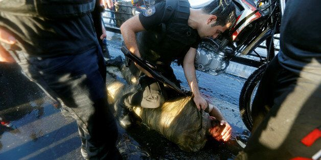 A policeman checks a soldier beaten by the mob after troops involved in the coup attempt surrendered...