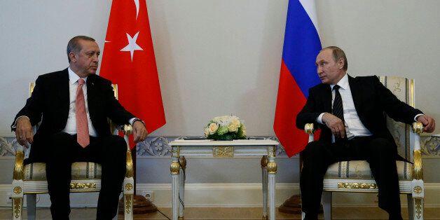 Russian President Vladimir Putin, right, and Turkish President Recep Tayyip Erdogan talk during their...