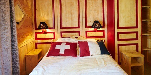 A bed lies directly across the French-Swiss border, with the head of the bed in Switzerland and the foot of the bed in France at the Hotel Arbez in Les Rousses April 23, 2014. Switzerland will vote on November 30 on an initiative from the group Ecopop which proposes a cap on the number of immigrants. The group says it is motivated by concerns about a lack of living space exerting too much pressure on the land and natural resources, rather than by opposition to foreigners. It proposes limiting immigration to just 0.2 percent of the resident population, equivalent to 16,000 people per year. This would represent a cut of more than 75 percent in annual net immigration from current levels. In Switzerland's system of direct democracy, any voter can trigger a referendum by collecting 100,000 signatures within 18 months. Picture taken April 23, 2014. REUTERS/Denis Balibouse (FRANCE - Tags: POLITICS ELECTIONS SOCIETY IMMIGRATION TPX IMAGES OF THE DAY)