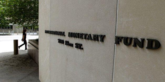 A pedestrians walks by the International Monetary Fund headquarters building in Washington on Sunday,...