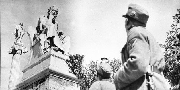 German troopers in their field grey uniforms look up at two ancient Greek statues on the Acropolis in...