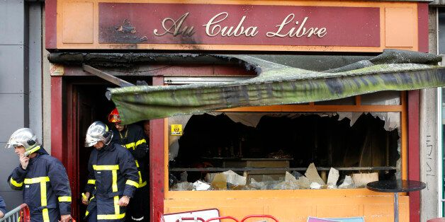 Firefighters leave the bar where a fire broke in Rouen, western France, Saturday Aug.6, 2016. A fire...