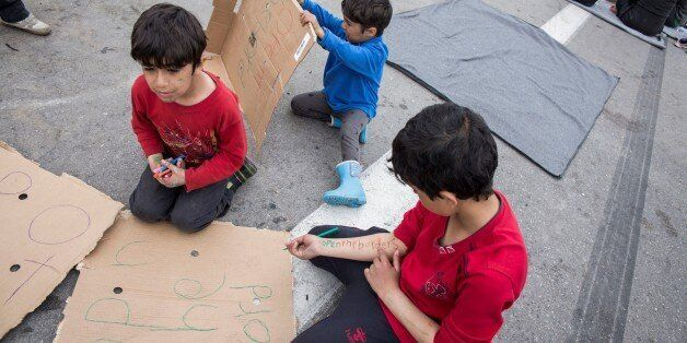 KILKIS, GREECE - APRIL 3: Refugee children prepare banners for the protests in EKO station at Polykastro...