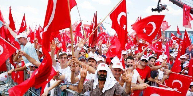 ISTANBUL, TURKEY - AUGUST 7: People hold Turkish flags as they arrive to take part in Democracy and Martyrs'...