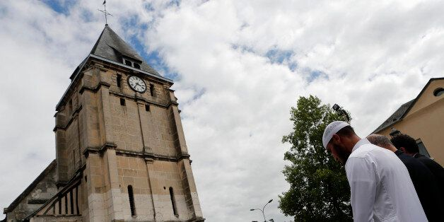 Muslim worshippers hold a minute of silence in front of the memorial at the Saint Etienne church in Saint-Etienne-du-Rouvray,...