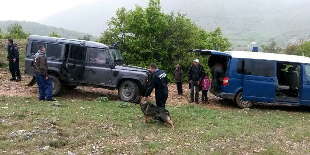 Albanian police officers detain Syrian migrants near the Albanian-Greek border near the city of Korca...