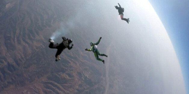 In this image made from a video provided by Mondelez International, Luke Aikins, center, skydives without...