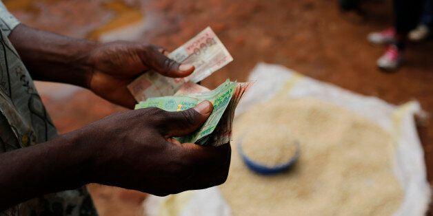 A Malawian trader counts money as he sells maize near the capital Lilongwe, Malawi February 1, 2016....