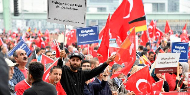 A Turkish protestor holds a banner reading 'Erdogan is a hero of democracy', left, during a demonstration...