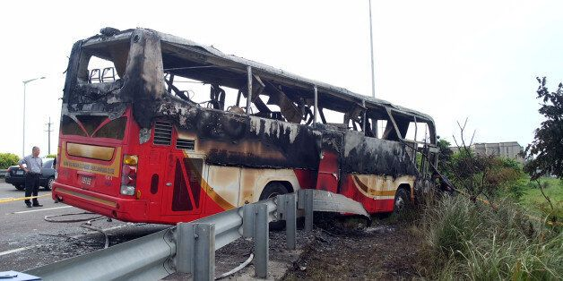 Investigators inspect a bus carrying tourists from mainland China that crashed and caught fire along...