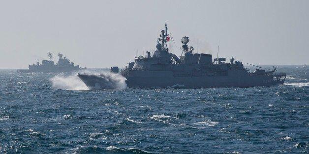 Turkish NATO warship TCG Turgutreis, foreground, maneuvers on the Black Sea after leaving the port of...