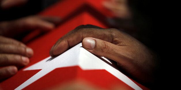 A hand rests on a coffin during a funeral service for victims of the thwarted coup at Fatih Mosque in...