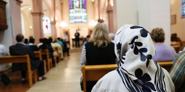 A Muslim faithful woman sits as she attends a Mass in tribute to priest Jacques Hamel at the Saint-Leu...