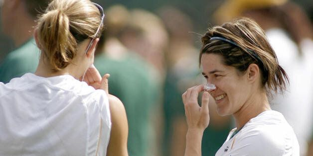 Australia's forward Sarah Walsh (R) chats with her teammate Dianne Alagich (R) while using sunblock before...