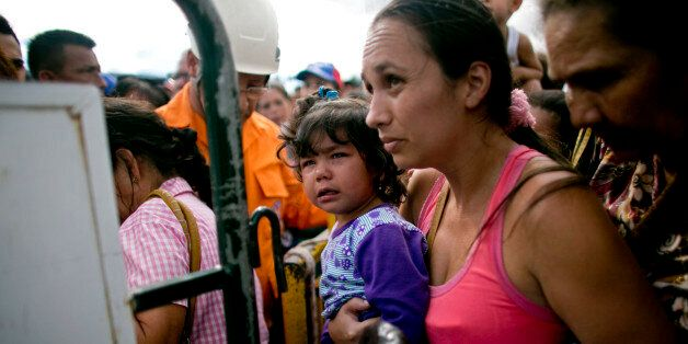 A woman carrying her daughter crosses into Colombia through the Simon Bolivar bridge in San Antonio del...