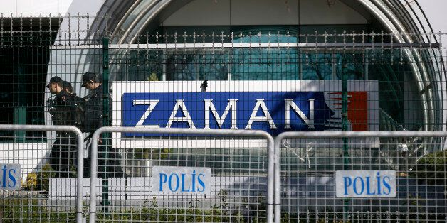 Riot police officers walk by the headquarters of Zaman newspaper in Istanbul, Sunday, March 6, 2016....