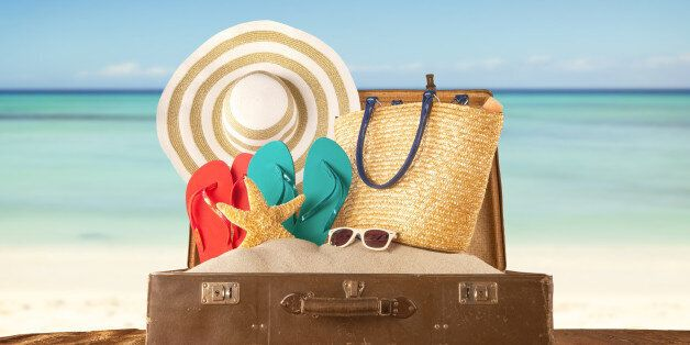 Travel concept with old suitcase on wooden planks full of beach accessories. Placed on mole with sandy...