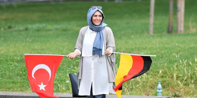 A Turkish woman holding a Turkish and a German flag waits for the start of a demonstration in Cologne,...
