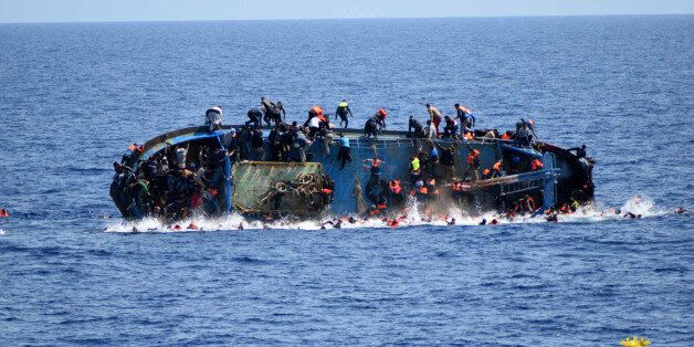 FILE - In this May 25, 2016 file photo made available by the Italian Navy, people try to jump in the...
