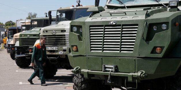 An employee walks next to KrAZ military vehicles at the Kremenchuk automobile plant (AutoKrAZ) in the...