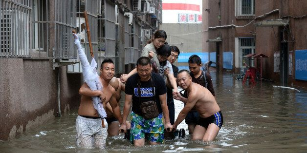 This photo taken on July 21, 2016 shows people making their way through a flooded area in Changping District...