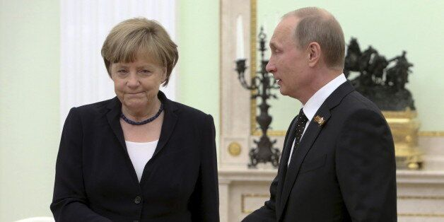 Russian President Vladimir Putin (R) approaches to shake hands with German Chancellor Angela Merkel during...