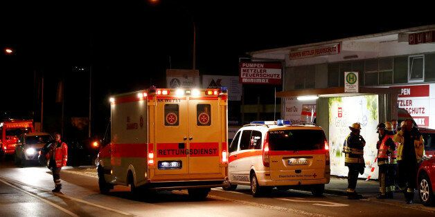 German emergency services workers work in the area where a man with an axe attacked passengers on a train...