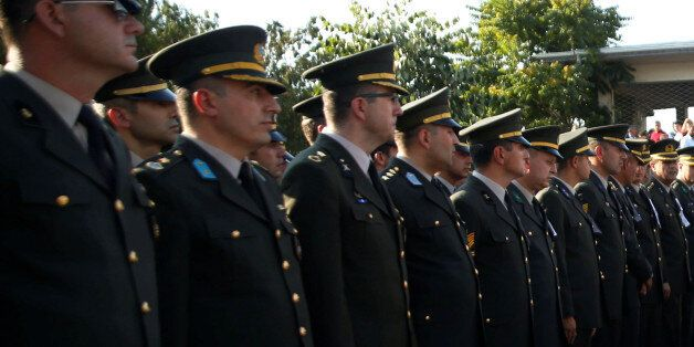Family members walk past Turkish army officers after a funeral service for the victims of the thwarted...
