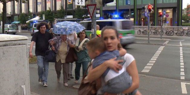 Members of the public run away from the Olympia Einkaufszentrum mall, after a shooting, in Munich, Germany,...