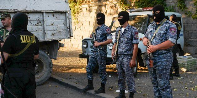 Police officers secure the area outside a police station seized by gunmen in Yerevan, Armenia, Saturday,...