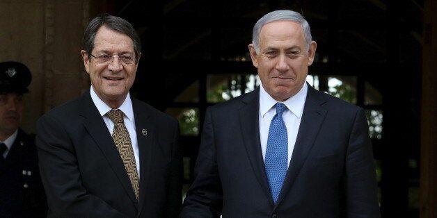 Cypriot President Nicos Anastasiades and Israeli Prime Minister Benjamin Netanyahu (R) shake hands outside...
