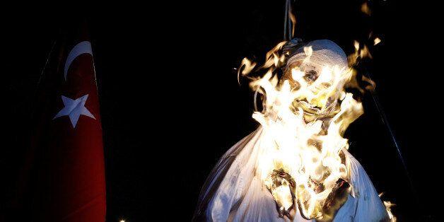 Supporters of Turkish President Tayyip Erdogan burn an effigy of U.S.-based cleric Fethullah Gulen hanged...