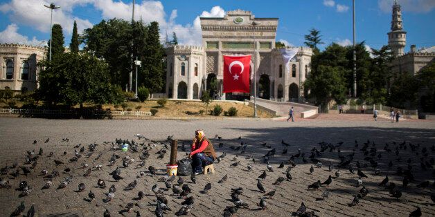 A woman waits for customers to sell food for pigeons outside the Istanbul University Tuesday, July 19,...