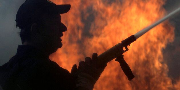 A fireman fights a forest fire in the Politia suburb north of Athens August 16, 2007. The fire fanned...
