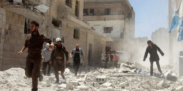 Civil Defence members work at a site hit by air strikes in Idlib city, Syria July 20, 2016. REUTERS/Ammar