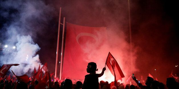 A young boy waves a Turkish national flag as supporters of Turkish President Tayyip Erdogan gather during...