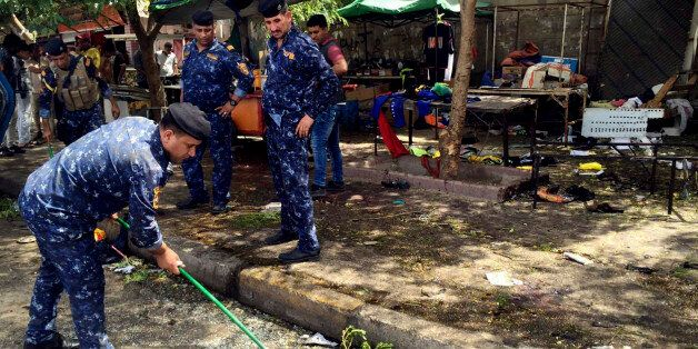 Iraqi security forces clean the scene of a bomb in Kadhimiyah district, Baghdad, Iraq, Sunday, July 24,...