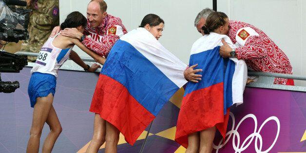 FILE - In this Aug. 11, 2012 file photo Russia coach Alexey Melnikov congratulates Olga Kaniskina, right,...