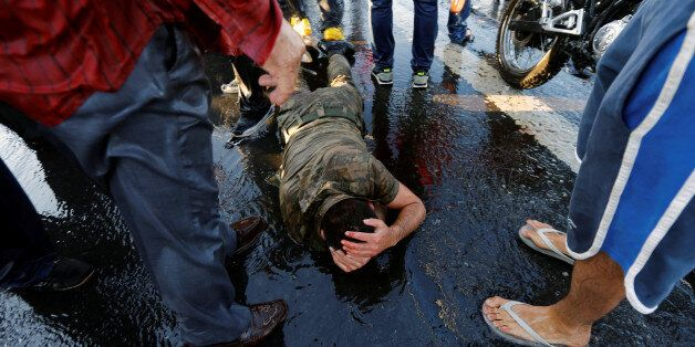 A soldier protects himself from the mob after troops involved in the coup attempt surrendered on the...