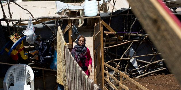 A Syrian woman enters the makeshift courtyard of her family's tent at Ritsona refugee camp north of Athens,...