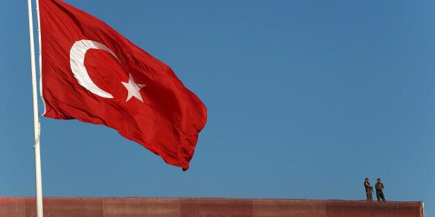 Police officers stand on a building roof overlooking a 'Republic and Democracy Rally' at Taksim square...