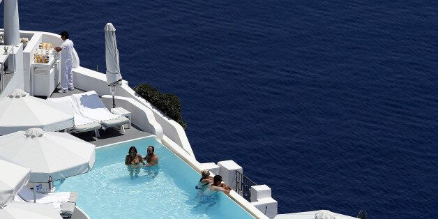 Tourists relax in a private swimming pool in the village of Oia on the Greek island of Santorini, Greece,...